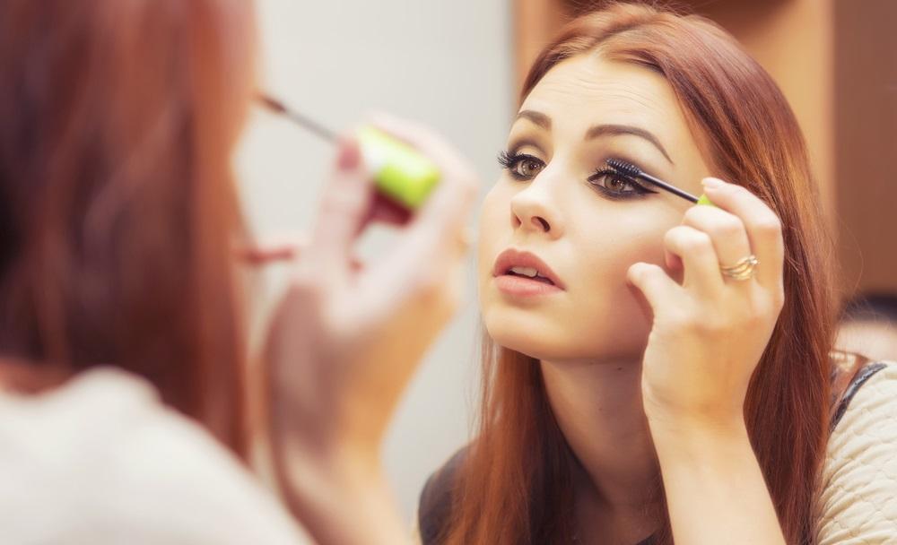 Woman putting mascara on
